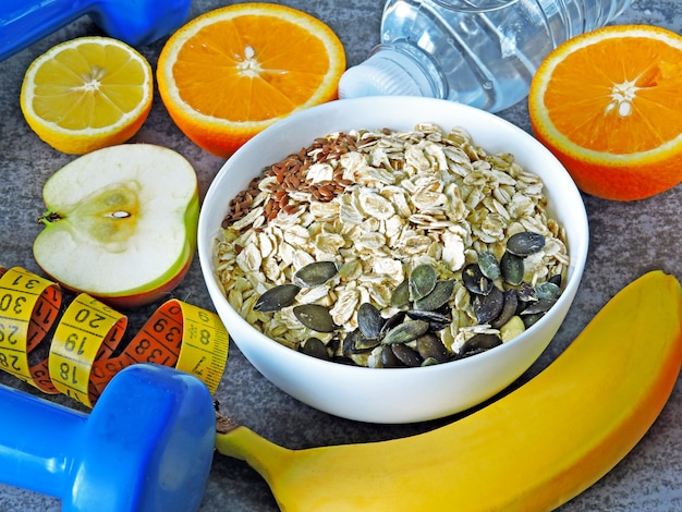 Oatmeal and seeds, water, fruit, dumbbells and measuring tape.
