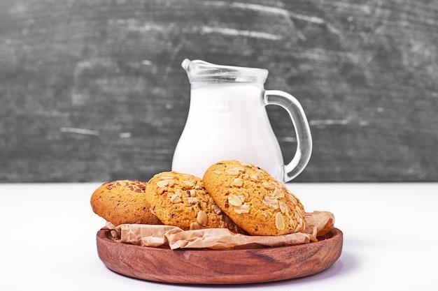 Farina d'avena e biscotti di sesamo con latte su bianco.