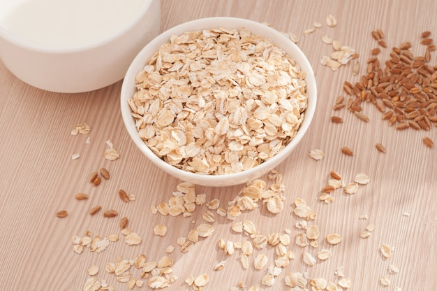 Oatmeal in a white bowl on wooden background near cup of milk