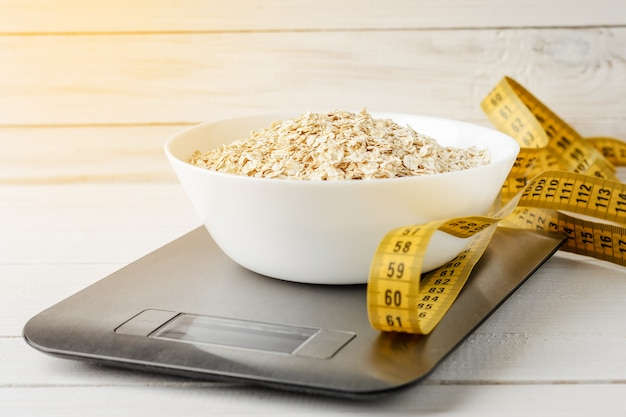 Oatmeal in a white plate on the kitchen scale