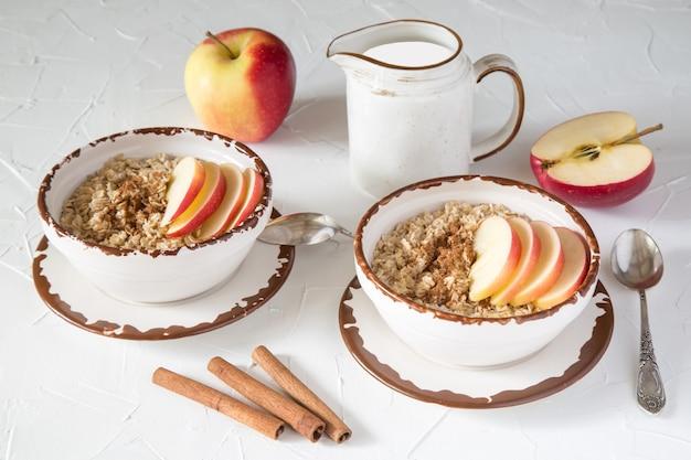 Овсяные хлопья с яблоком и корицей, молоко в красивой керамической посуде на белом столе. здоровое питание. диета, богатая клетчаткой. здоровый образ жизни