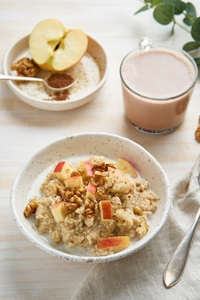 Oatmeal with apple, nuts, honey and cup of chocolate on white wooden light background.