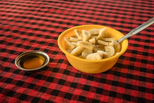 Овсяные хлопья с бананом и медом в миске на красной клетчатой скатерти Premium Фотографии