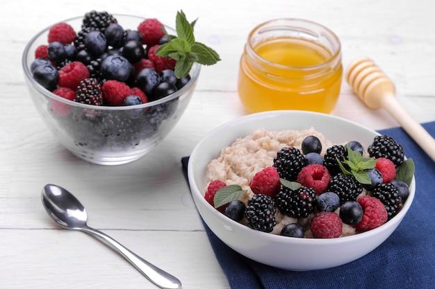 Овсяные хлопья с ягодами и медом в миске на белом деревянном столе. завтрак. здоровая пища.