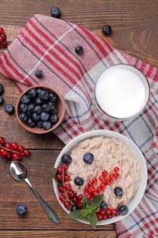 Овсяные хлопья с ягодами и молоком в миске на коричневом деревянном столе. завтрак. здоровая пища. вид сверху