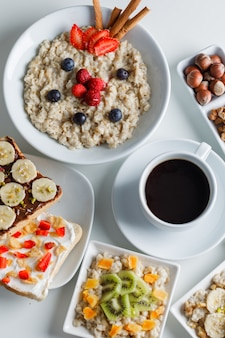 Oatmeal with berries, cinnamon, nuts, fruits, coffee, sandwich in plates