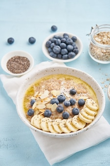 Oatmeal with blueberries, banana on blue light background.