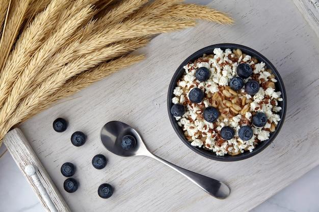 白く塗られた木製トレイにブルーベリーカードと亜麻の種子と小麦の穂が付いたオートミール。菜食