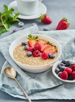 Oatmeal with blueberry, strawberry, raspberry on blue dark background.
