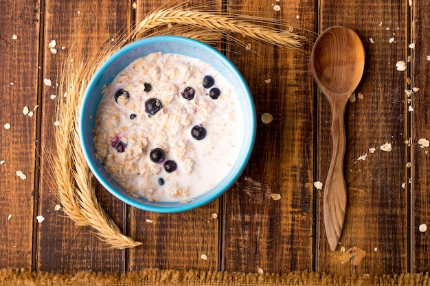 Oatmeal with currant in blue bowl with spoon on wooden background. rustic style. healthy breakfast. top view.