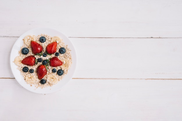 Oatmeal with different berries in bowl on wooden table