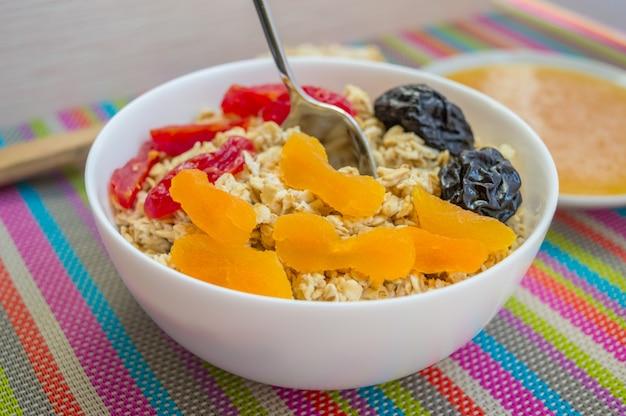 Овсяная каша с сухофруктами (абрикосы, кизил, чернослив) с медом в белой посуде. завтрак.