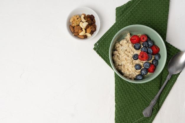 신선한 베리 과일을 곁들인 오트밀. 숟가락, 블루베리, 라스베리와 함께 그릇에 귀리 죽.