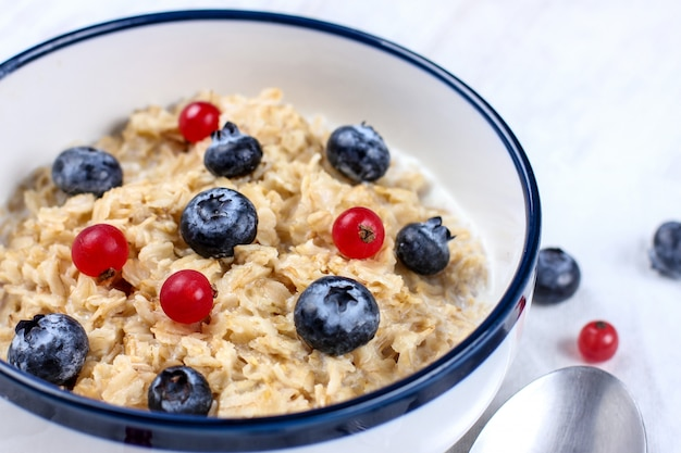 Oatmeal with fresh blueberries and red currant berries. diet food - oatmeal porridge in a plate with a spoon.