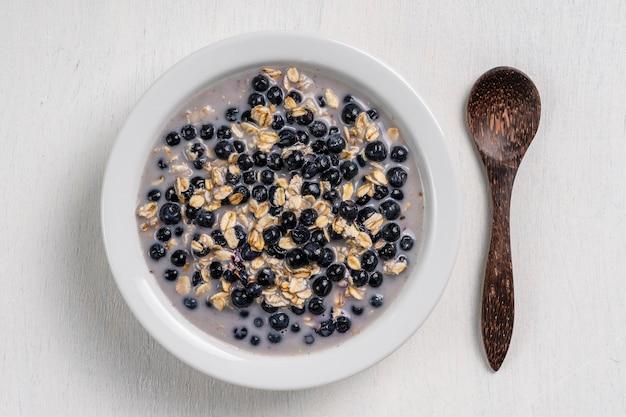 Овсяная каша со свежей черникой, миндальным молоком и медом на завтрак в белой тарелке на деревянных фоне. деревенский стиль. вид сверху. концепция здорового питания, суперпродукты