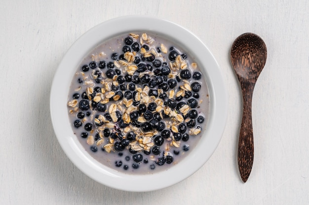 Oatmeal with fresh blueberry, almond milk and honey for breakfast in white plate on wooden background. rustic style. top view. the concept of healthy eating, superfood