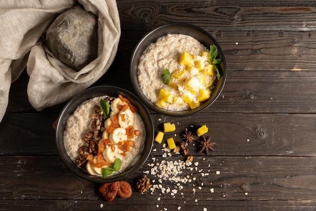 신선한 망고 조각, 바나나, 말린 살구 및 호두가 들어간 오트밀, 우유로 조리하고 민트 살구로 장식. 나무 식탁에 고전적인 채식 아침 식사 2 인분