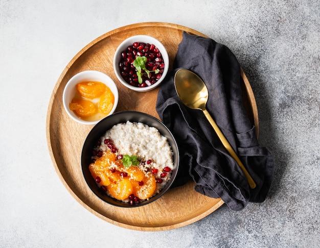 Овсяная каша со свежими кусочками мандарина и зернами граната, молотым миндалем и мятой в черной миске на деревянном круглом подносе. вид сверху