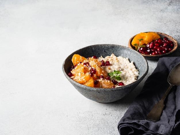 Овсяная каша со свежими кусочками мандарина и зернами граната, молотым миндалем и мятой в синей миске на сером фоне. копировать пространство