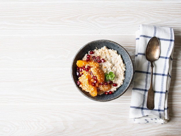 Овсяная каша со свежими кусочками мандарина и зернами граната, молотым миндалем и мятой в синей миске на белом фоне. копировать пространство вид сверху