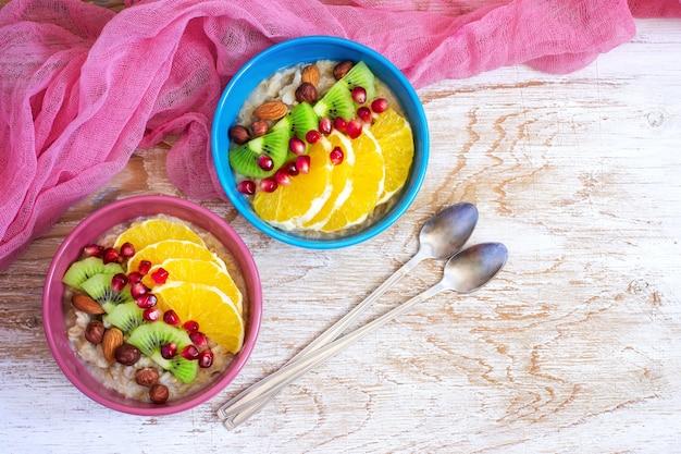 건강한 아침 식사를 위해 과일과 견과류를 곁들인 오트밀. 복사 공간이 있는 상위 뷰