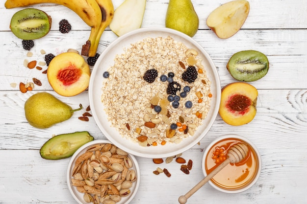 Oatmeal with fruit and honey on a white wooden table