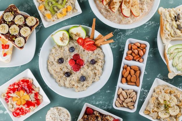 Овсяная каша с фруктами, вареньем, сэндвичем, корицей, орехами, овсяными хлопьями в тарелках