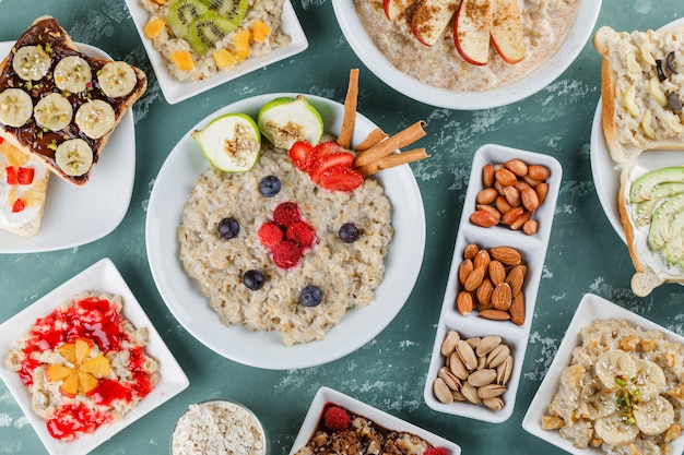 Oatmeal with fruits, jam, sandwich, cinnamon, nuts, oat flakes in plates