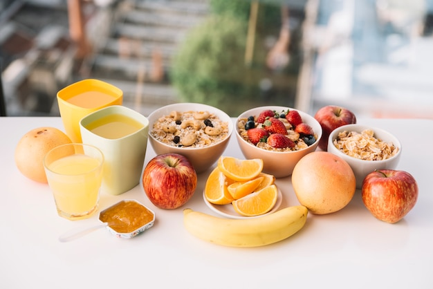 Oatmeal with fruits and juices on table