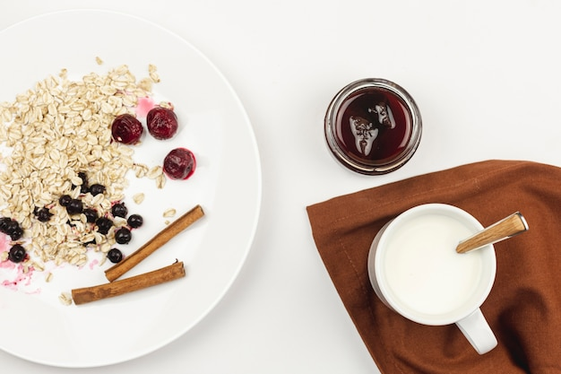 Oatmeal with jam and cinnamon sticks on a white plate