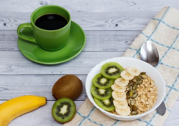 회색 나무 배경에 그릇과 녹색 커피 컵에 키위, 바나나, 호박 씨앗과 오트밀