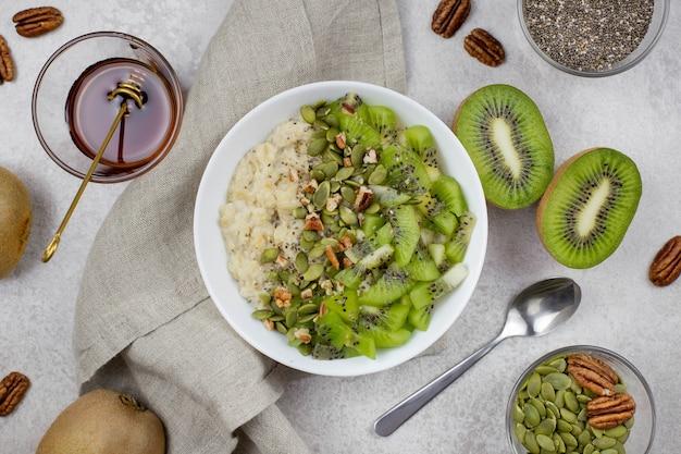 朝食用ボウルにキウイ、ピーカン、カボチャの種、チアシード、メープルシロップまたは蜂蜜を入れたオートミール