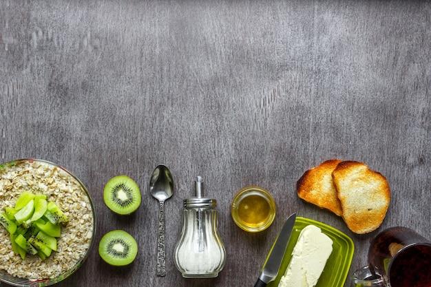 木製のテーブルにバターと蜂蜜とキウイトーストとオートミール健康的な朝食のコンセプト