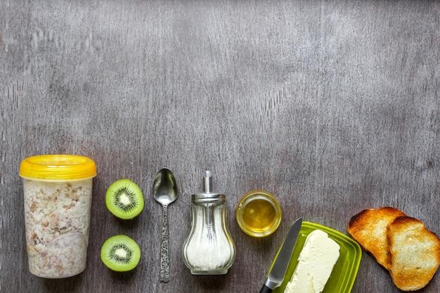 木製のテーブルにバターと蜂蜜とキウイトーストとオートミール