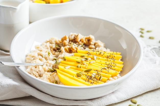 白いボウルにマンゴーとカボチャの種のオートミール。健康的な朝食、ビーガンフード。