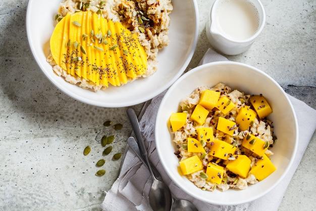 白いボウル、トップビューでマンゴーとカボチャの種のオートミール。健康的な朝食、ビーガンフード。