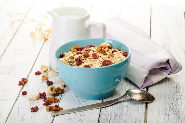 Овсянка с орехами и сухофруктами на старом деревянном столе покрашена белой краской. идеальный завтрак