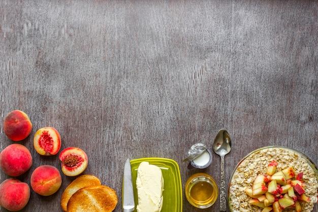 木製のテーブルにバターと蜂蜜を添えたピーチトーストのオートミールヘルシーな朝食のコンセプト
