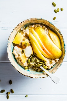 Oatmeal with pear and pumpkin seeds in ceramic bowl on white wooden surface, top view,