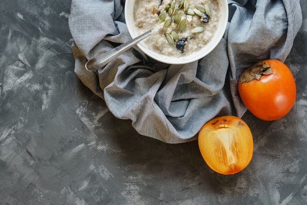 Oatmeal with persimmon on a gray rough surface
