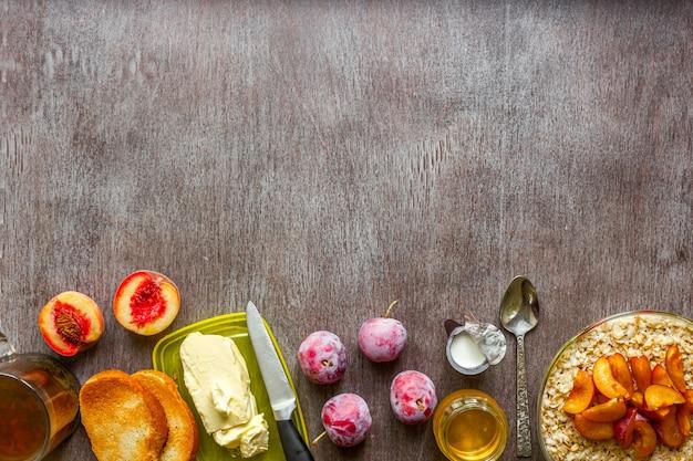 プラムとピーチのオートミール、バターとハチミツのトーストを木製のテーブルに。紅茶一杯。健康的な朝食のコンセプト。上面図。スペースをコピーします。静物。フラットレイ