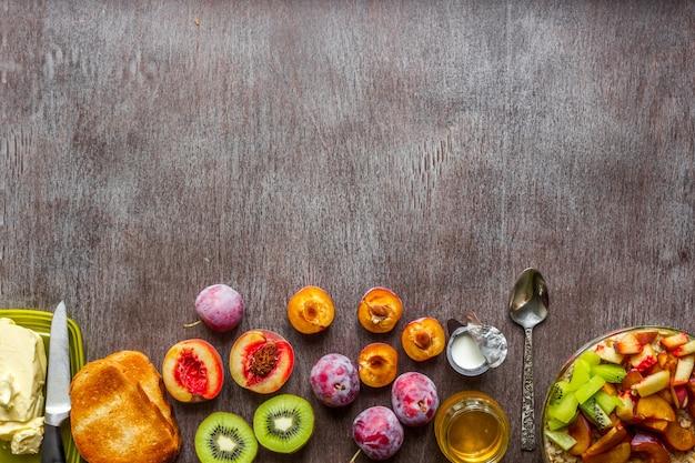 プラム、キウイ、ピーチのオートミール、バターとハチミツのトーストを木製のテーブルに。紅茶一杯。健康的な朝食のコンセプト。上面図。スペースをコピーします。静物。フラットレイ