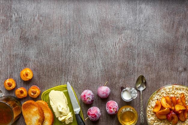 オートミールとプラム、トーストとバターと蜂蜜を木製のテーブルに。紅茶一杯。健康的な朝食のコンセプト。上面図。スペースをコピーします。静物。フラットレイ