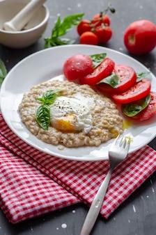 Овсяные хлопья с яйцом-пашот, помидорами и базиликом. свежие вкусные блюда правильного питания.