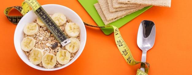 Овсяные хлопья с нарезанным бананом и хрустящими хлебцами лежат ложкой и желтой измерительной лентой на оранжевой поверхности