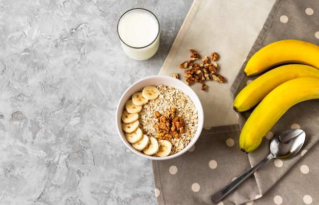 Oatmeal with sliced banana, walnuts and glass of milk on grey cement table for breakfast on linen napkins