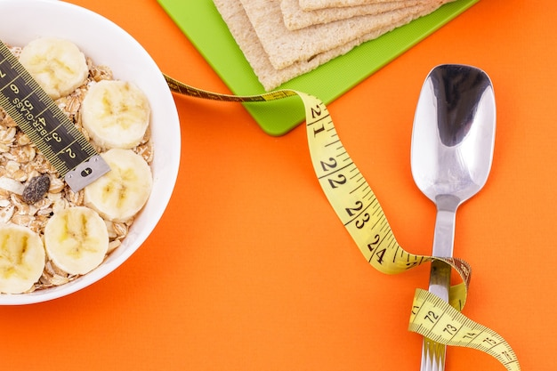 Oatmeal with sliced bannana and crispbread lie with spoon and yellow measuring tape on orange surface healthy food and dita concept
