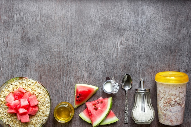 木製のテーブルにスイカとオートミール健康的な朝食の概念