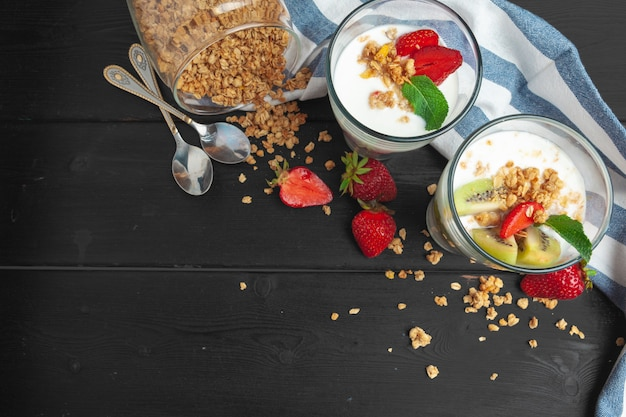 Oatmeal with yogurt and berries on a black wooden surface , top view, healthy breakfast,