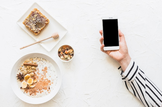 Oatmeals; dryfruits and honeycomb on table with cellphone in hands